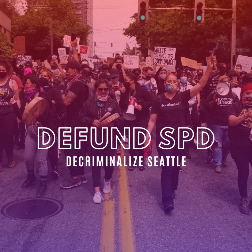 """Image description: The front of a 12,00 person march, image shows protestors in the street with streetlight and green trees above, Black and Indigenous leaders of march hold drums and megaphones. Many people's hands in the air or holding signs, masked faces, some shirts reading Block the Bunker and Decolonize. Overlay on image reads """"Defund SPD, Decriminalize Seattle"""""""