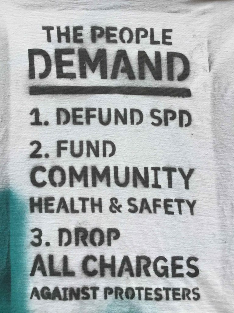 "Image description: Stencil with black ink on white and teal background reads ""The People Demand 1. Defund SPD 2. Fund Community Health & Safety 3. Drop All Charges Against Protesters"